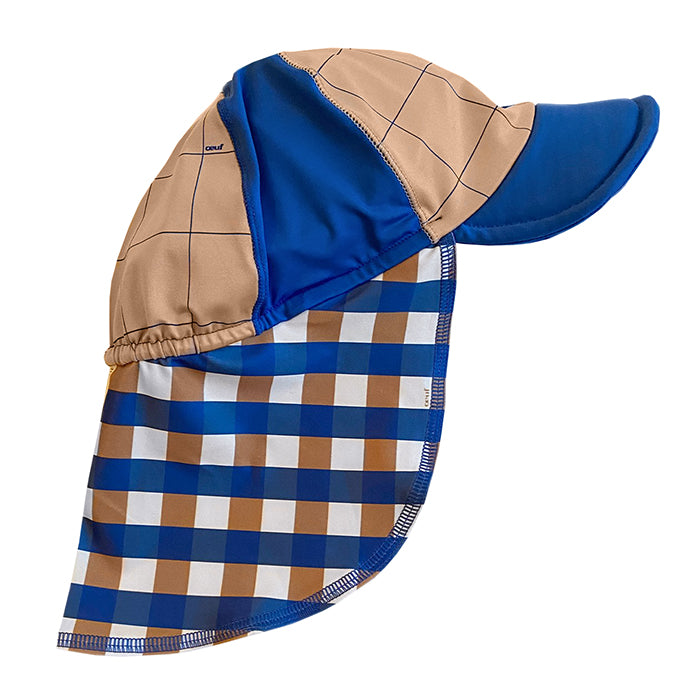 Baseball cap with attached neck covering in a swimsuit-style fabric has a blue and beige gingham pattern.