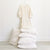 Cream muslin dress with buttons down the front and cuffed long sleeves hanging above a stack of pillows.