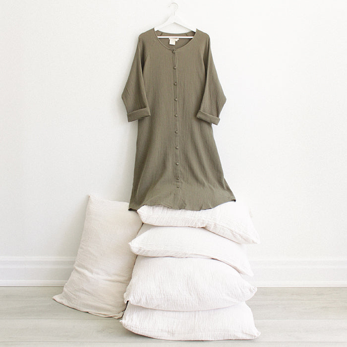Khaki green muslin dress with buttons down the front and long sleeves hanging above a stack of pillows.
