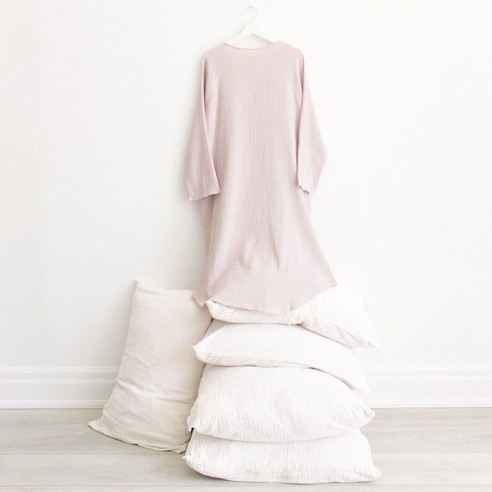Light pink muslin dress with buttons down the front and long sleeves with a hand in the pocket hanging above a stack of pillows.