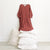 Red brown muslin dress with cuffed long sleeves hanging above a stack of pillows.