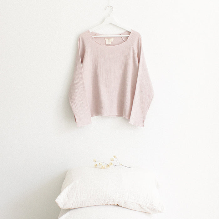 Light pink muslin shirt with long sleeves hanging above a stack of pillows.