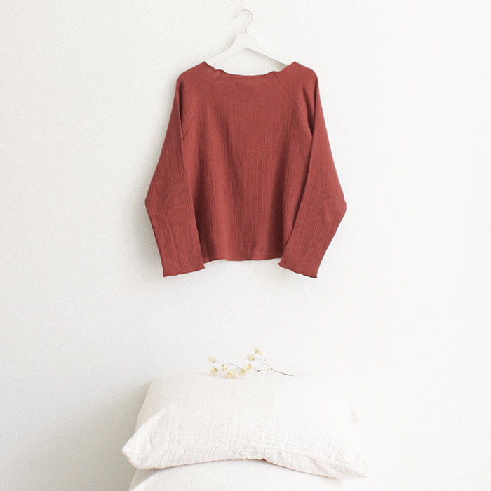 Red brown muslin shirt with cuffed long sleeves hanging above a stack of pillows.