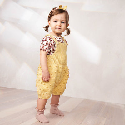 Baby standing wearing short overalls with a textured knit dot pattern in pale yellow.