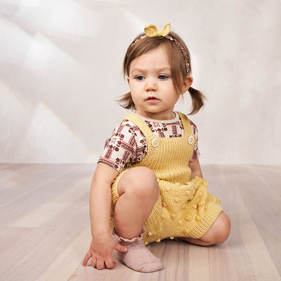 Baby sitting wearing short overalls with a textured knit dot pattern in pale yellow.