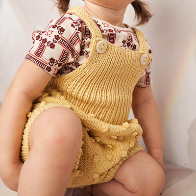 Baby wearing short overalls with a textured knit dot pattern in pale yellow.