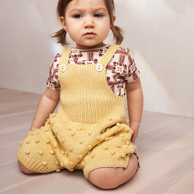 Baby kneeling wearing short overalls with a textured knit dot pattern in pale yellow.