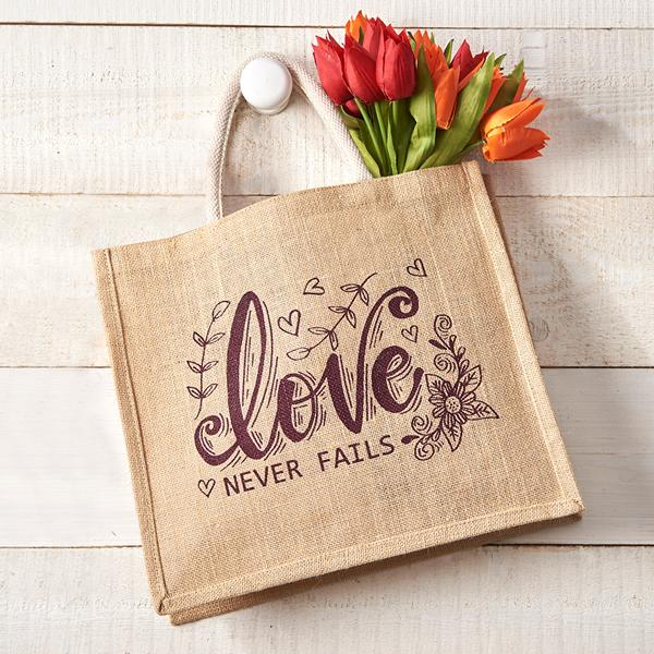 Love Never Fails Jute Bag - shown on a peg with tulips
