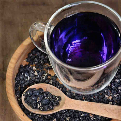 Dark purple Goji berry tea in a clear glass mug, with a wooden plate and spoon full of Black Goji berries.