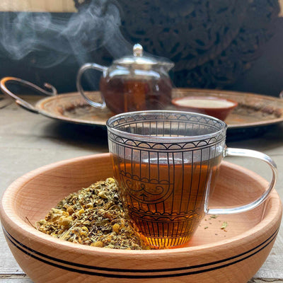 Steam coming from a glass teacup in a wood bowl with loose tea on the side. A glass teapot and tea tray are in the background.