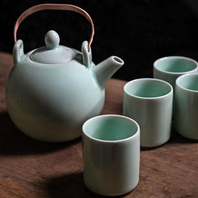 Light green colored teapot and four teacups on a wooden surface with a dark backdrop.