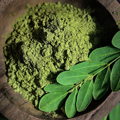 A close-up of the top-view of Green Moringa powder in a dark wood bowl with fresh moringa leaves.