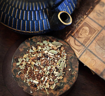 A dish of loose Red Rooibos Spice Chai Tea sits next to a dark blue teapot and old notebook on a dark wood surface.