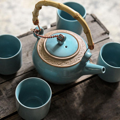 A blue teapot with a brown accent and a bamboo handle, with four blue teacups on a wooden surface.
