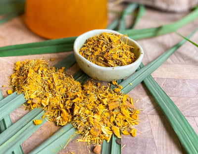 Loose turmeric lemongrass tea overflows from a small white bowl and onto lemongrass leaves. A pitcher of tea is in view on a wooden surface.