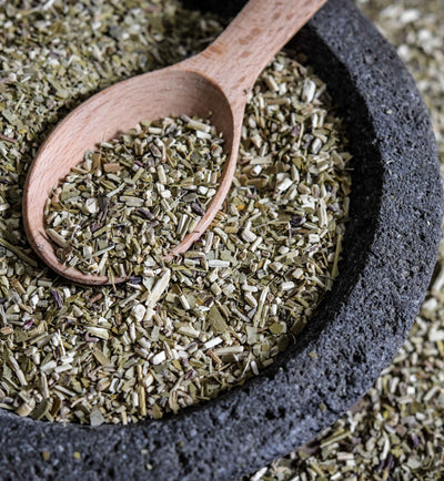 Cut and sifted Yerba Mate tea sits in a dark stone bowl with a wooed spoon. More yerba mate can be seen to the side of the bowl.