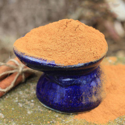 Cinnamon powder overflowing off of a dark blue dish with a blurred background.