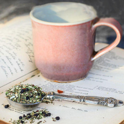 A fancy tablespoon of Double E Immune tea overflows on an open book, and an empty pink and white cup is in the background.