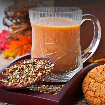 A mahogany tray holds a spoon overflowing with loose Gingersnap Tea and a glass mug with tea. Fall décor can be seen and a gingersnap cookie.