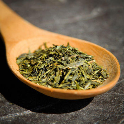 A closeup of Sencha Green Tea on a wooden spoon, on a dark surface.