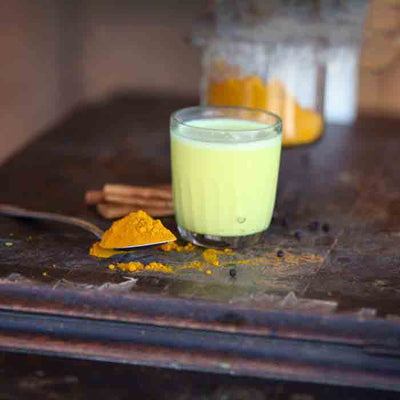 An overflowing spoon of turmeric powder sits to the side of a clear glass of turmeric milk. More spices are seen in the background and it all rests on a dark wood surface.