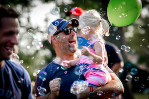 Father and daughter having a blast at a bubble party