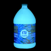 Gallon of Tekno Bubbles® Gold under blacklight