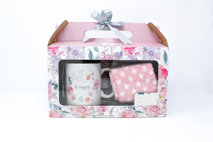 Floral gift box with 'Be happy' mug and pink and white polka dot fluffy socks inside.
