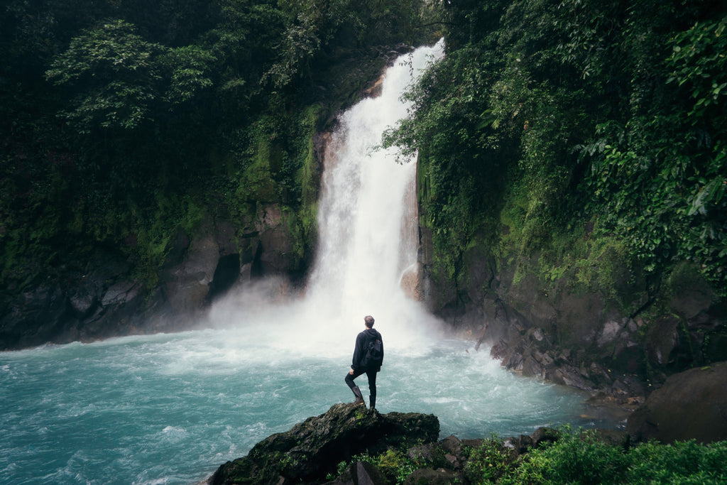 man standing on cliff near falls photo