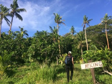 young woman travels and hikes in tropical terrain