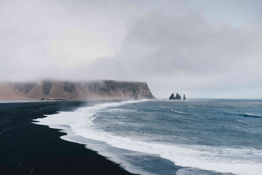 black sand near body of water under the cloudy sky during daytime photo