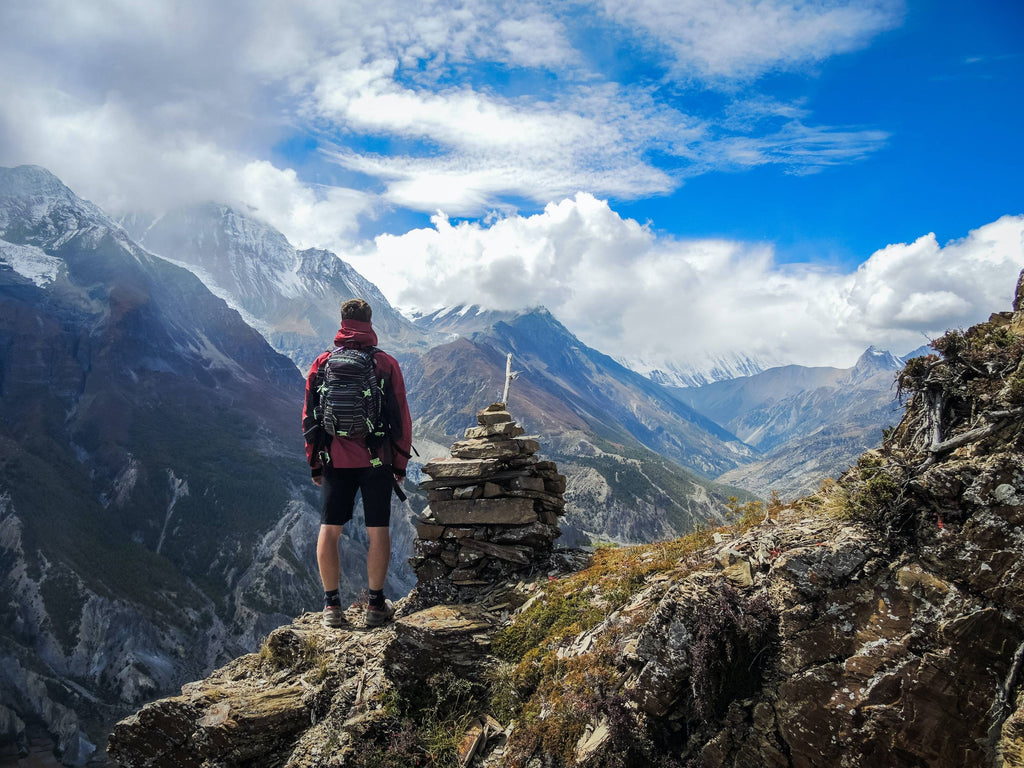 man standing on top of mountain beside cairn stones photo