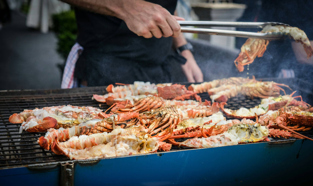 man grilling crabs during daytime photo
