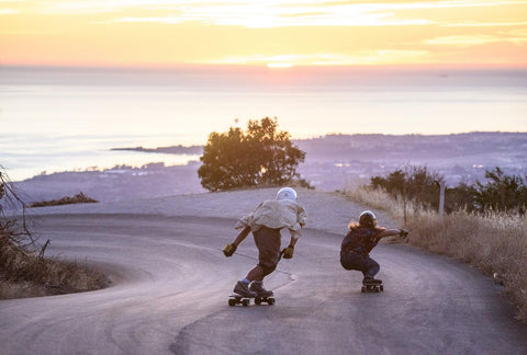 Downhill longboarding in the sunset
