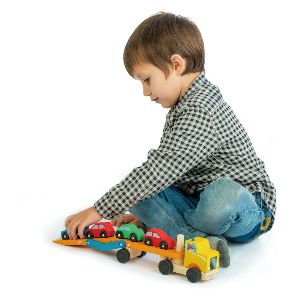 Boy playing with Tender Leaf Toys Car Transporter