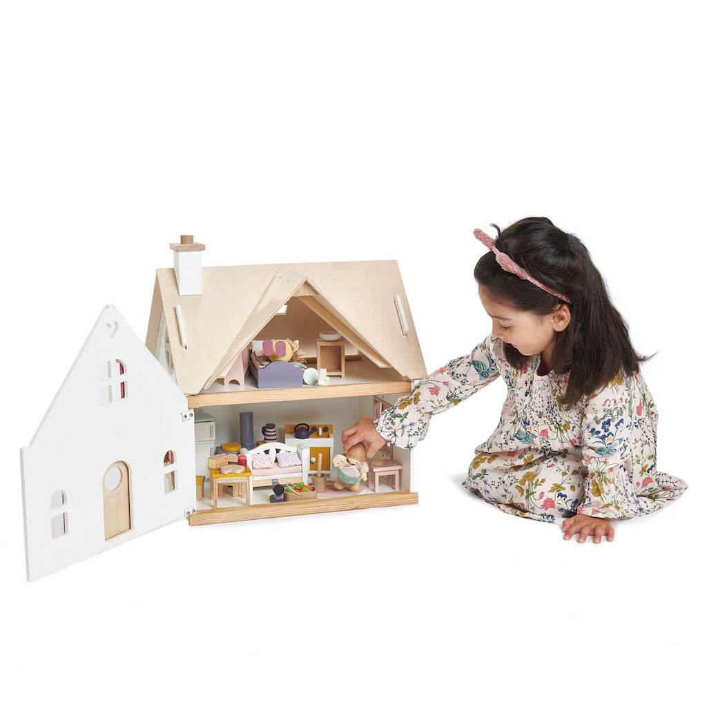 Girl playing with the Tender Leaf Toys Cottontail Cottage Dolls House