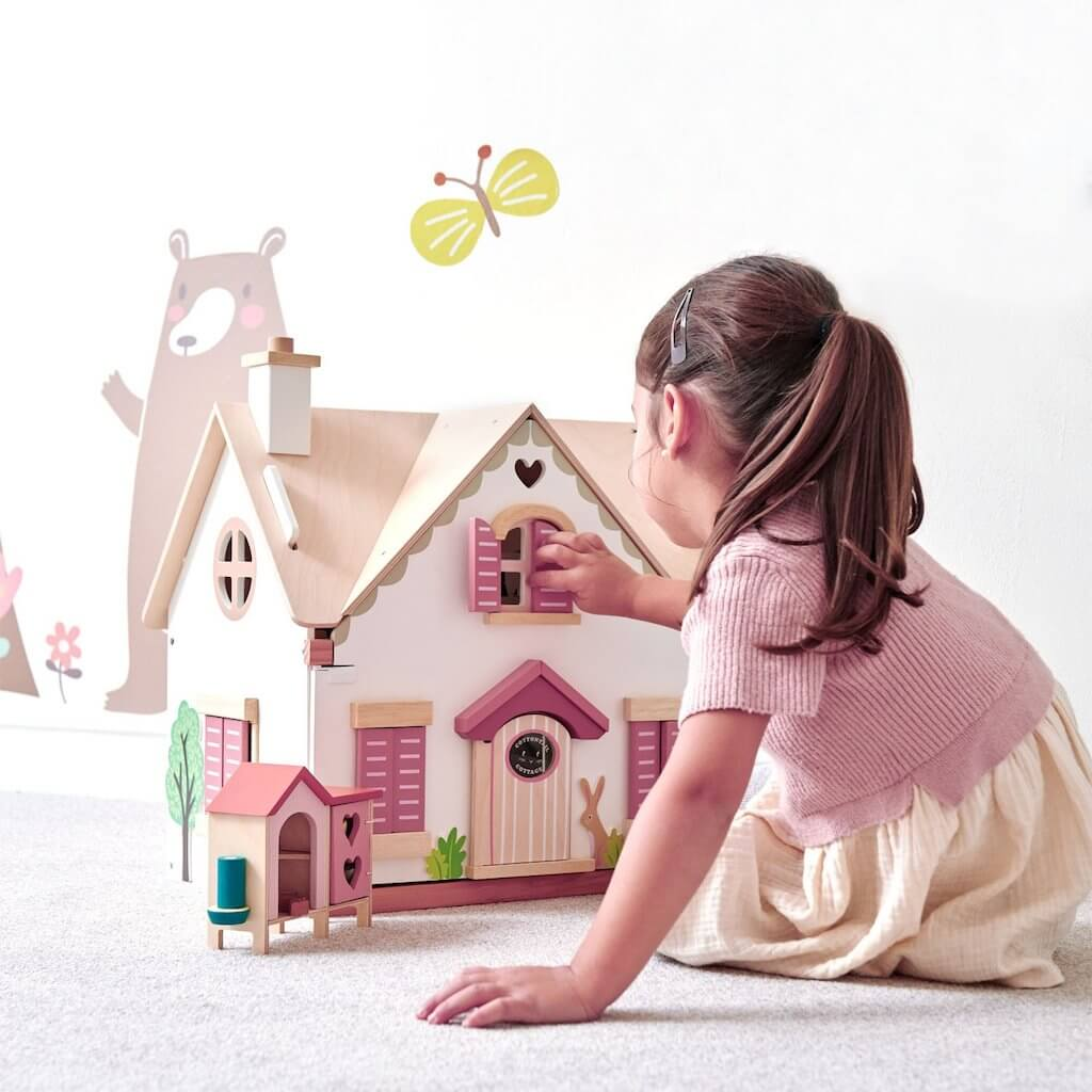 Girl opening the window on the Tender Leaf Toys Cottontail Cottage Dolls House