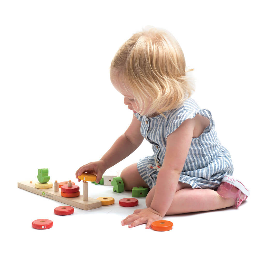 Girl playing with the Tender Leaf Toys Counting Carrots