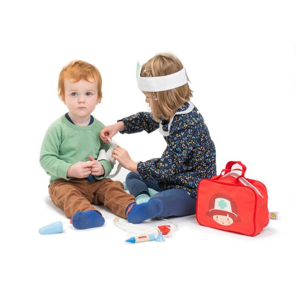 Girl bandaging boys arm with Tender Leaf Toys Doctors & Nurses Set