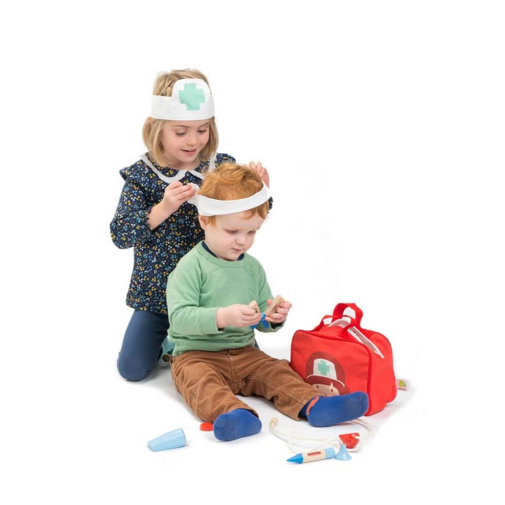 Girl bandaging boys head with Tender Leaf Toys Doctors & Nurses Set