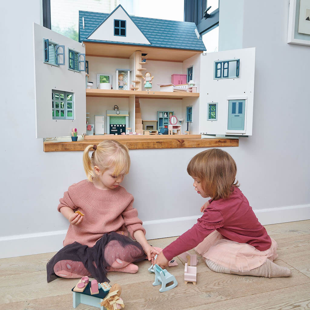 Two girls playing with the Tender Leaf Toys Dovetail Dolls House
