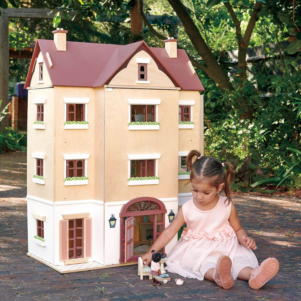 Girl playing with the Tender Leaf Toys Fantail Hall Dolls House