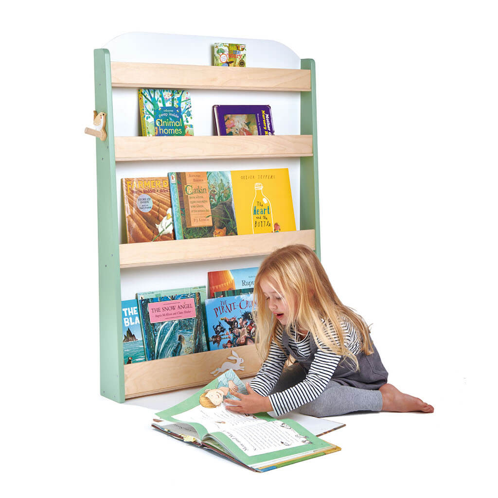 Tender Leaf Toys Forest Bookcase filled with books next to a girl reading on the floor