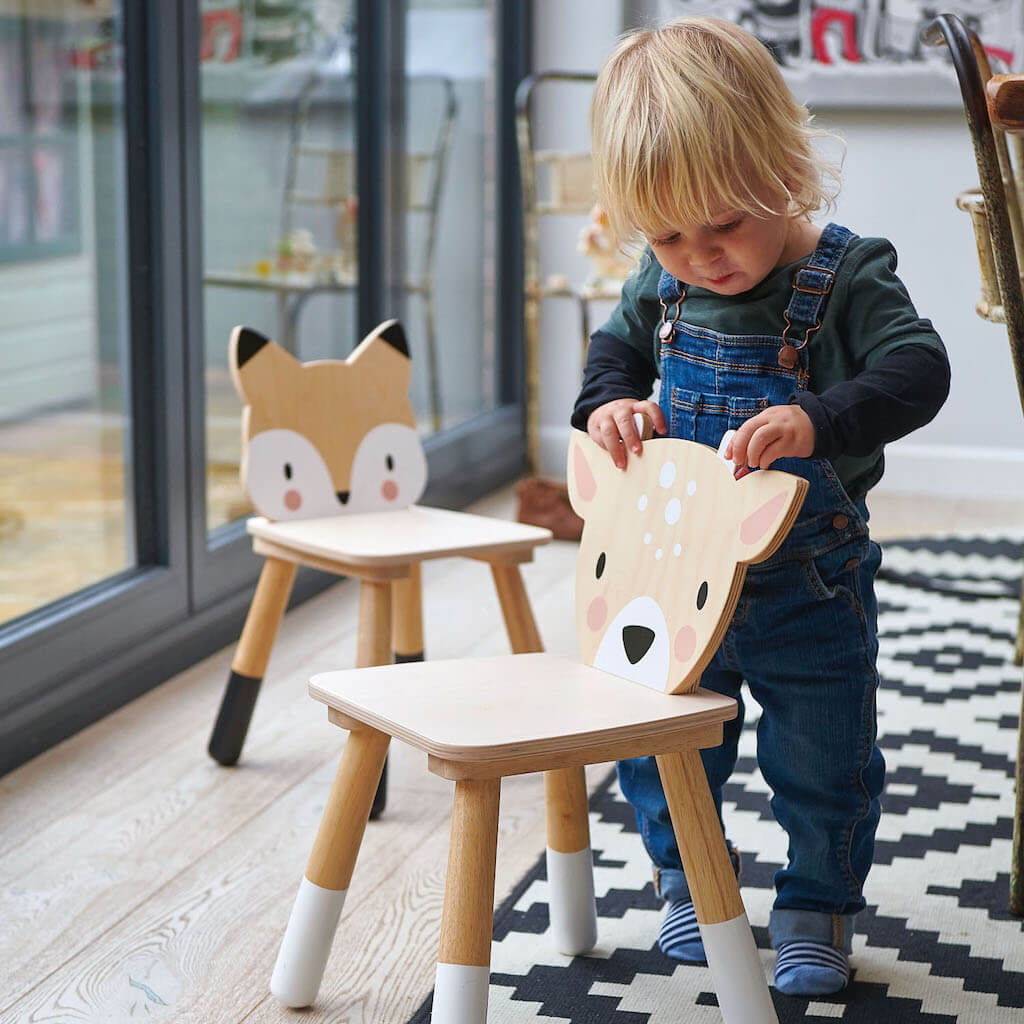 Lifestyle image of a boy holding the Tender Leaf Toys Forest deer Chair with the Forest Fox Chair in the background