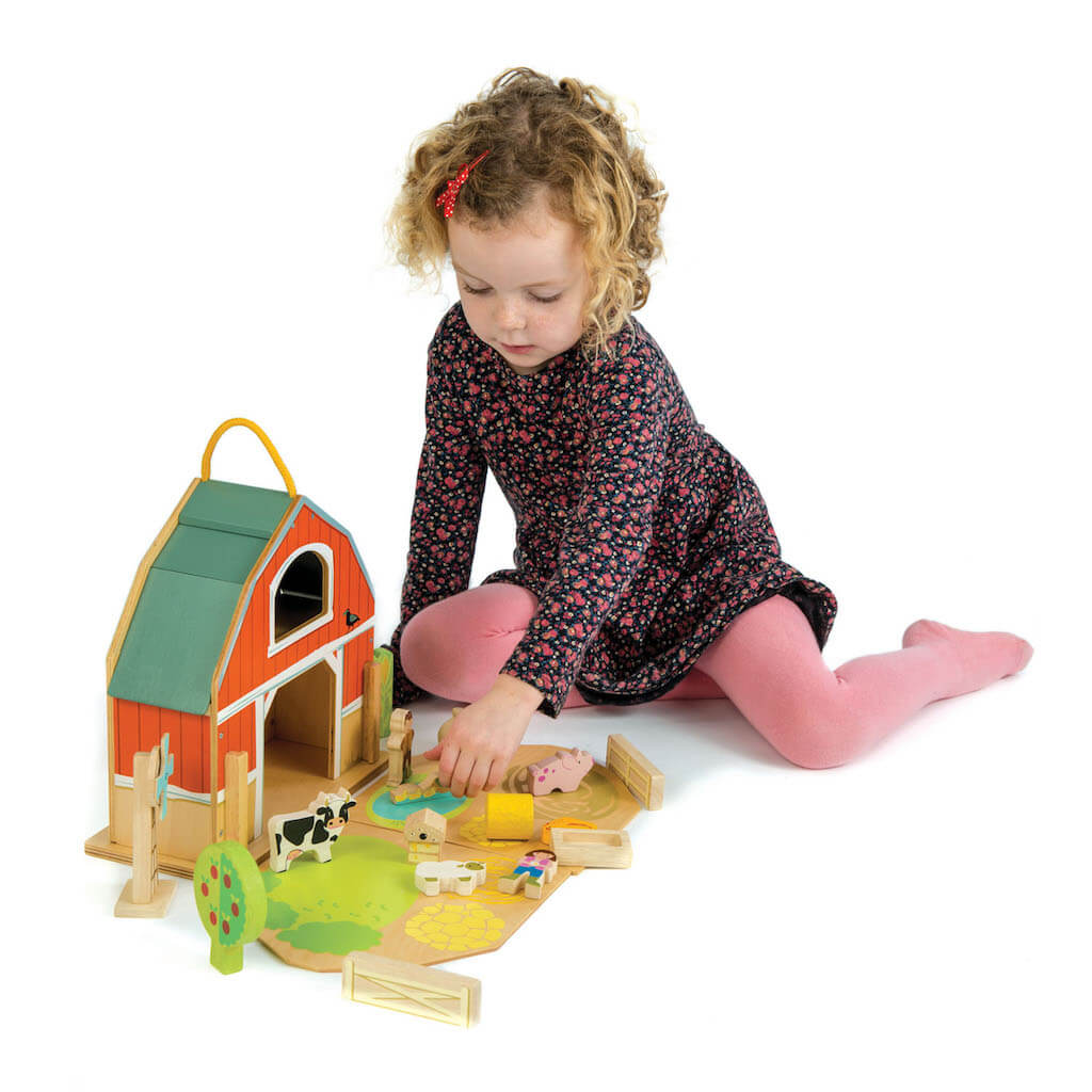 Girl playing with the Tender Leaf Toys Little Barn Set