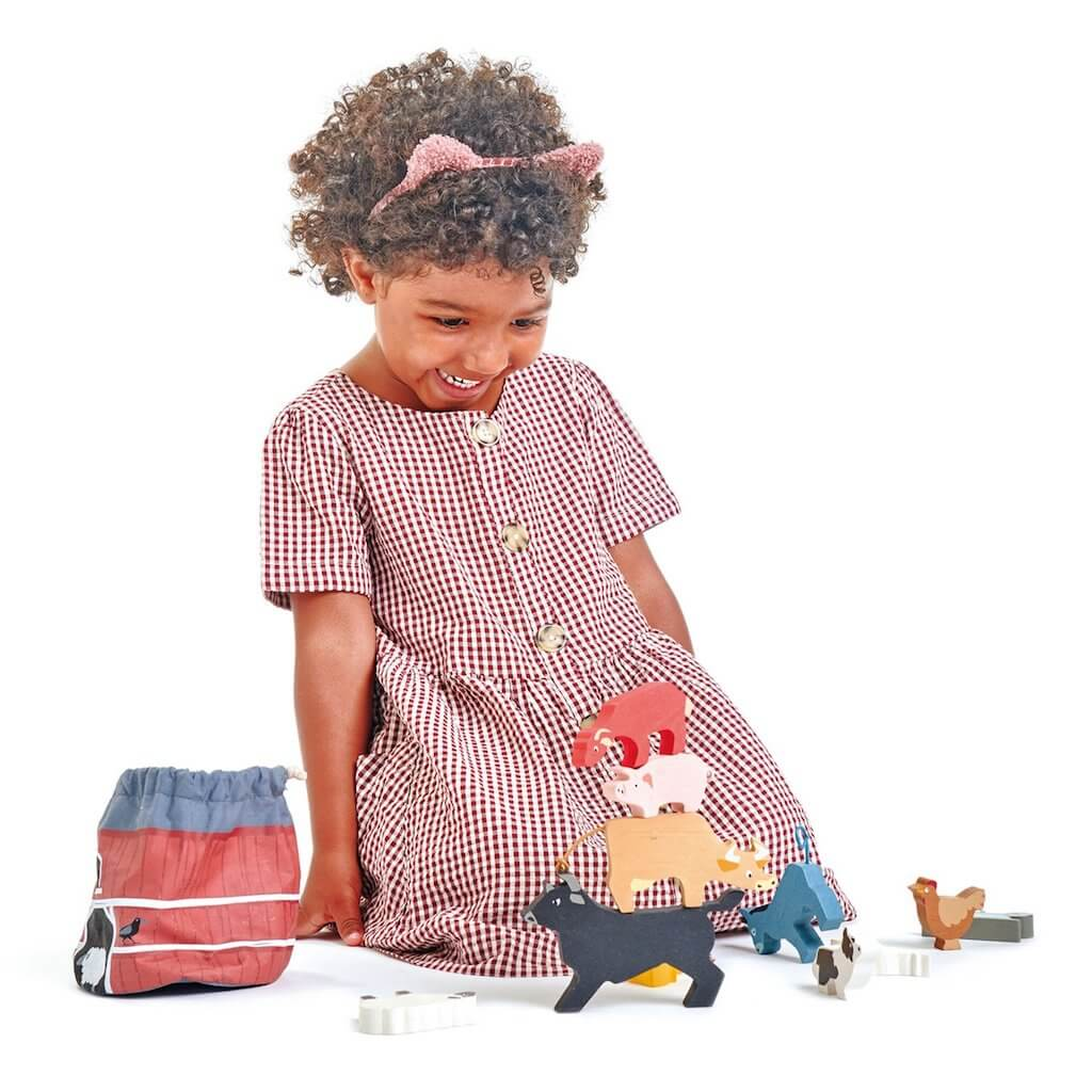 Girl playing with the Tender Leaf Toys Stacking Farmyard