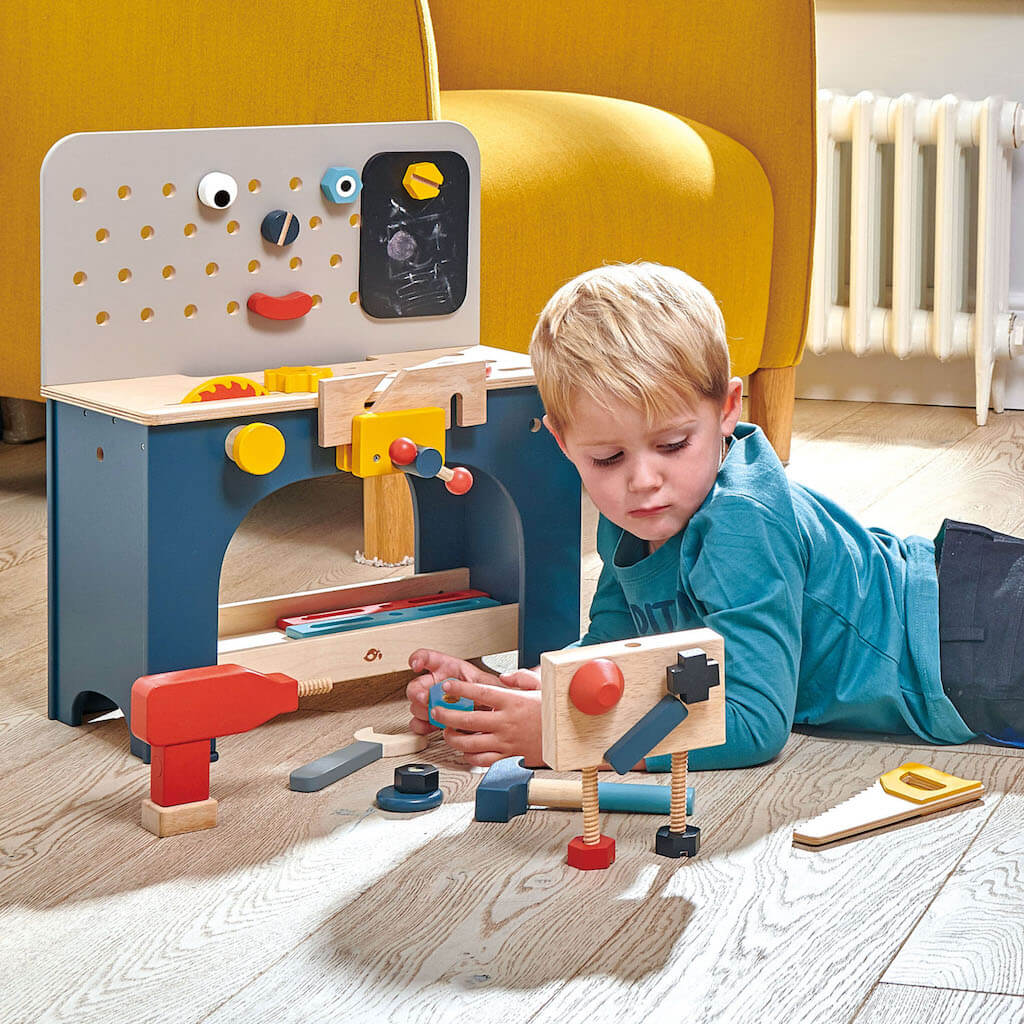 Boy playing with the Tender Leaf Toys Table Top Tool Bench
