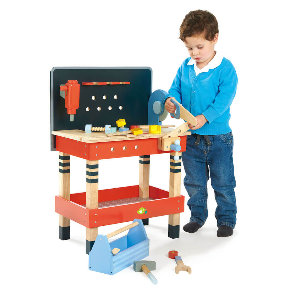 Boy playing with the Tender Leaf Toys Tool Bench