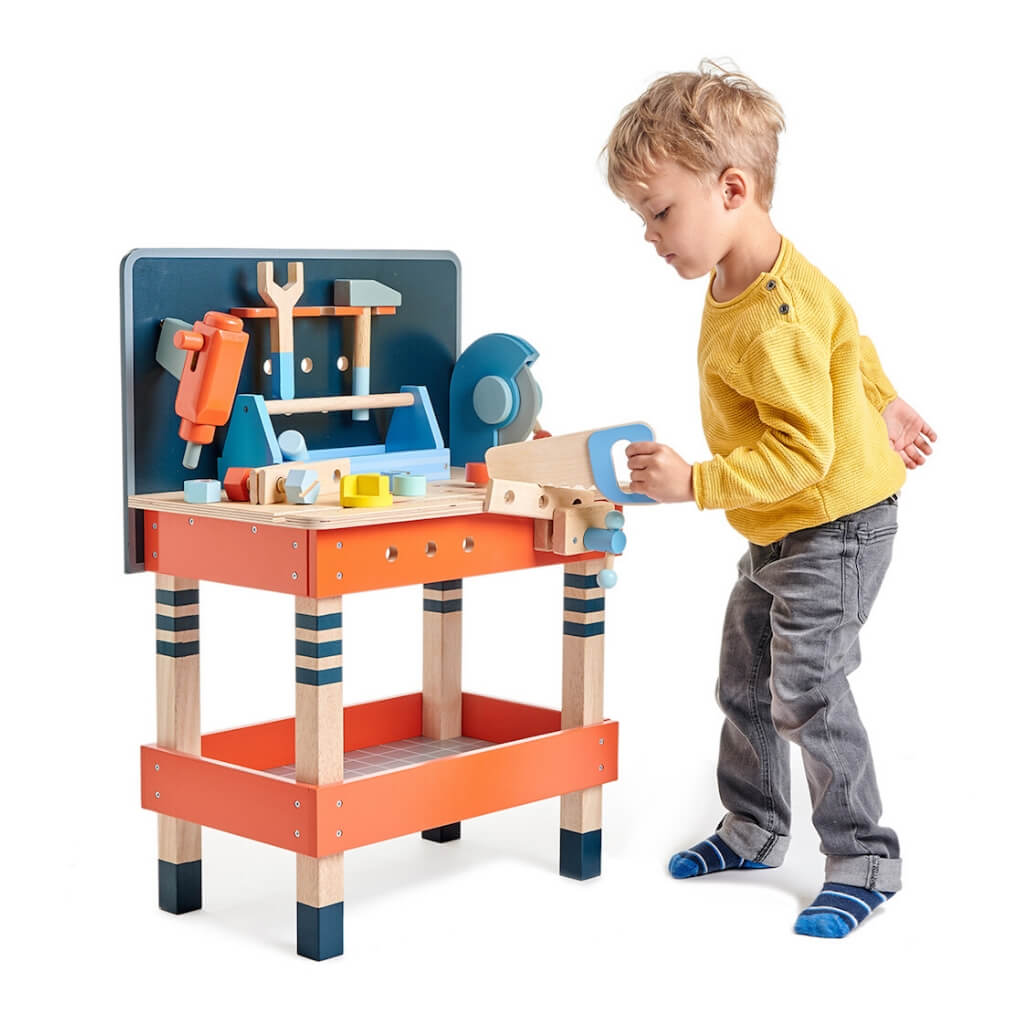 Boy sawing with the Tender Leaf Toys Tool Bench