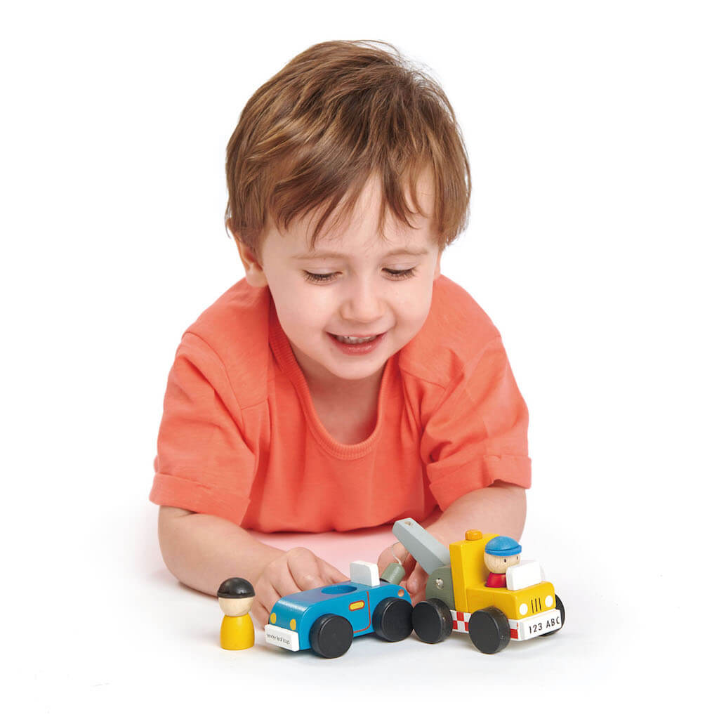 Boy playing with the Tender Leaf Toys Tow Truck